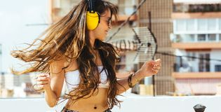 Cheerful woman with long hair, with yellow headphones listens to Stock Images