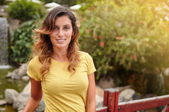 Cheerful woman looking at camera with confidence. While standing by park lake royalty free stock image