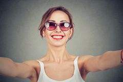 Cheerful woman looking at camera and taking selfie on gray background. stock images