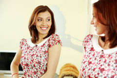 Cheerful woman looking on her reflection in the mirror Royalty Free Stock Photos