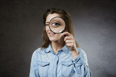 Cheerful woman looking through magnifying glass royalty free stock photography