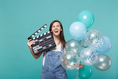 Cheerful woman looking up holding classic black film making clapperboard, celebrating with colorful air balloons