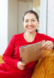 Cheerful  woman looks newspaper Royalty Free Stock Photography