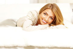 Cheerful woman lying on the bed Stock Images