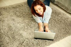 Cheerful woman lying on the carpet and typing on the laptop Royalty Free Stock Photography