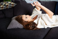 Cheerful woman lying on a cosy couch Stock Photo