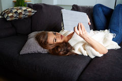 Cheerful woman lying on a cosy couch Royalty Free Stock Images