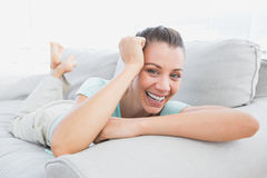 Cheerful woman lying on couch smiling at camera Royalty Free Stock Images