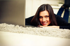 Cheerful woman lying with laptop Royalty Free Stock Images