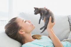 Cheerful woman lying on sofa holding a grey kitten Stock Photos