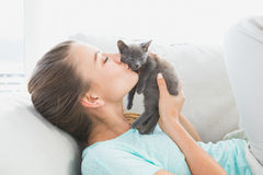 Cheerful woman lying on sofa kissing a grey kitten Royalty Free Stock Photo