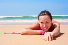 Cheerful woman lying on the wet sand Stock Image