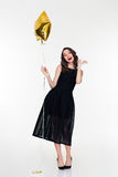 Cheerful woman with makeup in retro style holding golden balloon Stock Photography