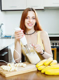 Cheerful woman  making milk shake with bananas Stock Photo