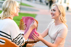 Cheerful woman making present to mom Stock Photos