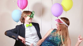 Cheerful woman and man dancing in photo booth. Cheerful beautiful woman and smiling man dancing in party photo booth stock video footage