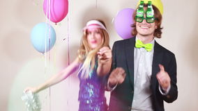 Cheerful woman and man dancing in photo booth. Cheerful beautiful woman and smiling man dancing in party photo booth, graded stock video footage
