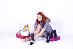 Cheerful woman measures the shoes Stock Image