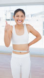 Cheerful woman measuring waist while gesturing thumbs up Stock Images