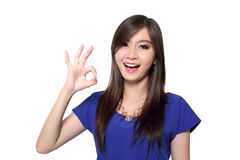 Cheerful woman with okay hand sign. Beautiful young Asian woman with big bright smile making okay hand gesture while looking at camera, isolated on white Royalty Free Stock Images
