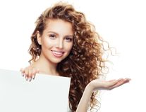 Cheerful woman with open hand and white empty board background with copy space for advertising marketing or product placement.  stock photography