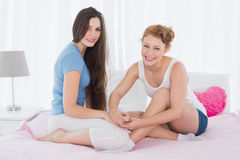 Cheerful woman painting friends nails on bed Royalty Free Stock Photo