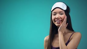 Cheerful woman in pajamas applying face cream, softening and toning skin. Stock footage stock footage
