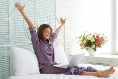 Cheerful woman in pajamas at the bedside with hands lifted and l. Cheerful young woman in pajamas is sitting at the bedside with her hands lifted and laptop on Stock Images
