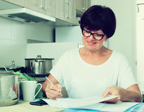 Cheerful woman paying bills Stock Image
