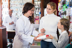 Cheerful woman pharmacist helping customers Royalty Free Stock Photography
