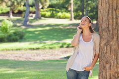 Cheerful woman on the phone leaning against a tree Royalty Free Stock Images
