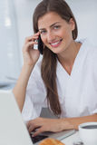 Cheerful woman phoning and using her laptop Stock Images