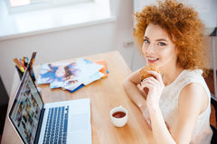Cheerful woman photographer using laptop, drinking coffee and eating cookies Stock Photo