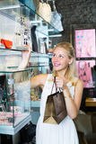 Cheerful woman picking earrings in jewellery boutique Royalty Free Stock Photography