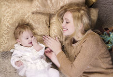 Cheerful woman playing with baby girl Royalty Free Stock Photos