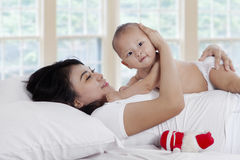 Cheerful woman playing with child on bed Royalty Free Stock Images