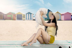 Cheerful woman playing with dog. Cheerful young woman and her dog sitting on the mat with beach huts background Stock Image