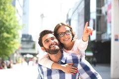 Cheerful woman pointing away while enjoying piggyback ride on man in city Stock Photos