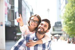 Cheerful woman pointing away while enjoying piggyback ride on man in city Royalty Free Stock Photo