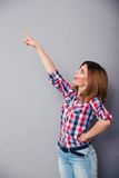 Cheerful woman pointing finger up Stock Images