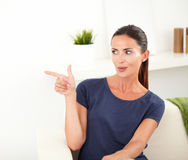Cheerful woman pointing while looking away Stock Image