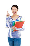 Cheerful woman pointing up while holding files Royalty Free Stock Photo