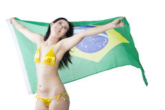 Cheerful woman posing with Brazilian flag. Happy sexy woman wearing bikini while holding Brazilian flag in the studio, isolated on white background Royalty Free Stock Photography