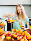 Cheerful woman pouring beverages with fruits Stock Photos