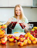 Cheerful woman pouring beverages with fruits Stock Image