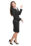 Cheerful woman presenting and showing copy space. Cheerful excited businesswoman in black skirt suit presenting and showing copy space. Very happy smiling full Royalty Free Stock Photos