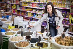 Cheerful woman purchasing lentil in shop. Cheerful long-haired woman purchasing lentil in shop Royalty Free Stock Photos