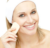 Cheerful woman putting foundation cream Stock Images