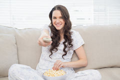 Cheerful woman in pyjamas having popcorn while watching tv Royalty Free Stock Image
