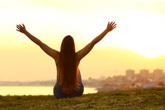 Cheerful woman raising arms at sunset Royalty Free Stock Photography